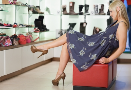 Woman sitting on a stool admiring shoes in boutique photo