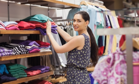 Woman putting jumpers on shelf in boutique photo