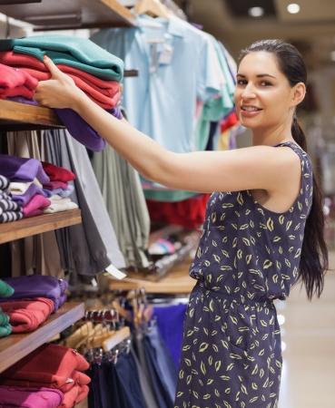 Woman putting jumpers on shelf and smiling in boutique photo