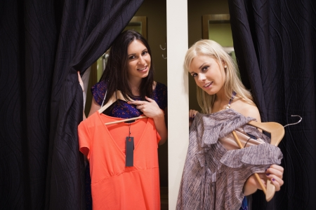 Women stadning in the changing room holding up clothes photo
