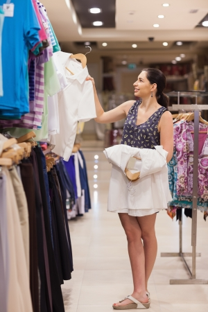 Woman holding white shirts on hangers in clothing store photo