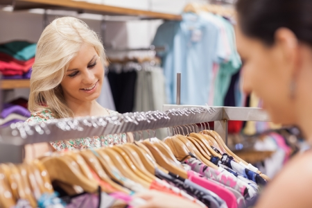 Woman looking at the clothes rack and smiling with friend Stock Photo - 15592041