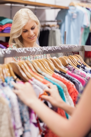 Woman searching at the clothes rack while smiling  photo