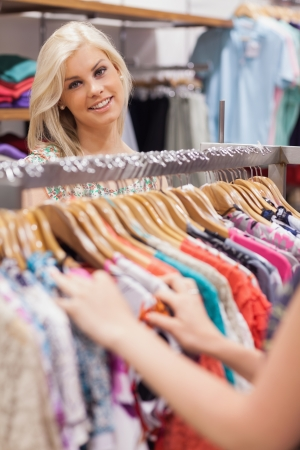 Woman standing at the clothes rack of a boutique smiling photo