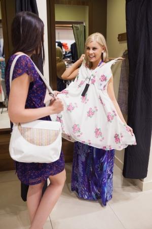 changing clothes: Mujer de pie en el vestuario de una tienda de ropa muestra con un amigo