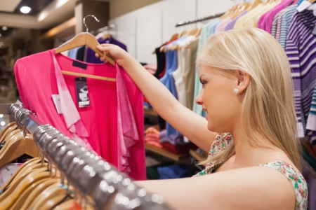 Woman looking at clothes in a boutique while standing at a clothes rack  photo