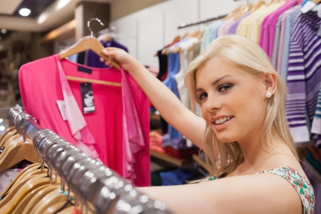 Woman is in a boutique while standing at a clothes rack looking at clothes Stock Photo - 15592684