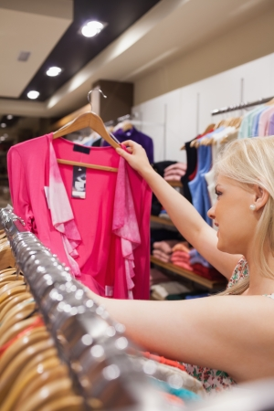 Woman is searching for clothes at a clothes rack in a boutique photo