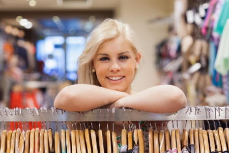 Woman is leaning at a clothes rack while smiling  photo
