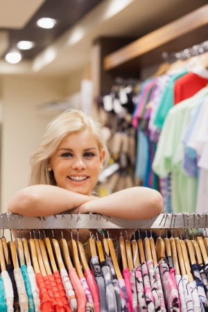 Woman is leaning at a clothes rack of a boutique while smiling  photo