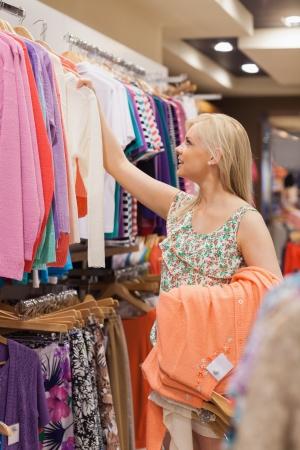 kledingwinkel: Vrouw die kleren uit de kleren rek Stockfoto