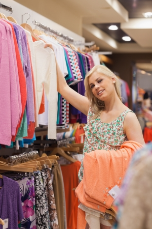 Woman is searching for clothes and smiling in shopping mall Stock Photo - 15584975