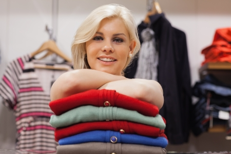 Woman leaning on clothes at a boutique smiling  photo