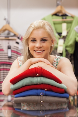 Woman is leaning on clothes in a boutique and smiling  photo