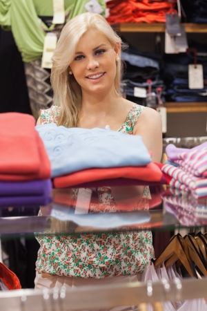 Woman standing at a clothes rack in a boutique smiling  photo