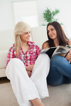 adult magazines: Women sitting on the floor talking and looking at magazine