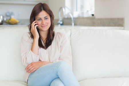 Woman sitting on the couch using her phone at home photo