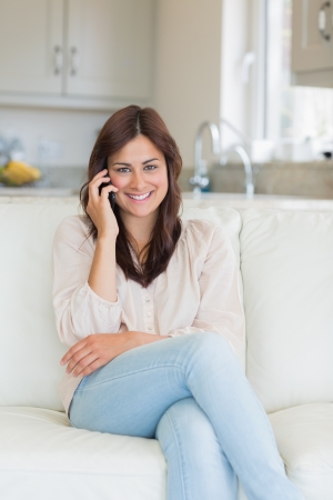 Woman phoning and sitting on the couch in the living room photo