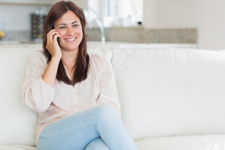 Woman phoning while sitting on the couch in the living room photo