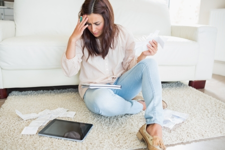 solicitous: Woman with tablet pc calculating bills on the carpet Stock Photo