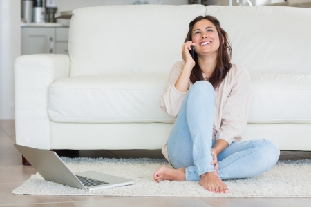 Smiling woman on the phone in front of laptop in living room photo