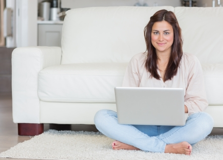 Happy woman with laptop on living room floor photo