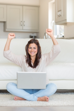 Happy and successful woman raising her hands in front of laptop photo