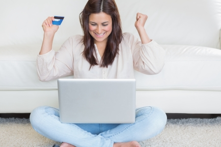 Happy woman buying something in the internet in living room photo