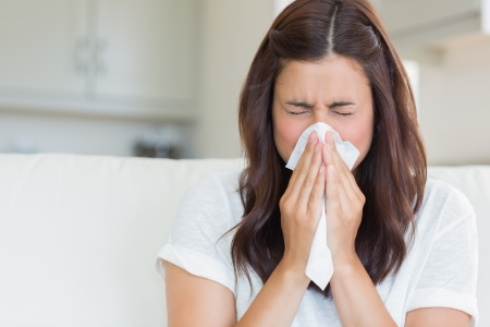 cold woman: Brunette sneezing in a tissue in the living room