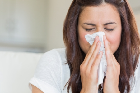 tejido: Burnette mujer sonarse la nariz en el tejido Foto de archivo