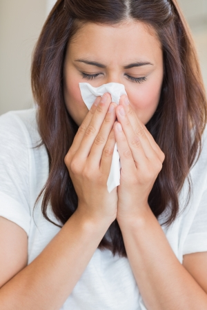 snort: Sick woman with tissue on sofa