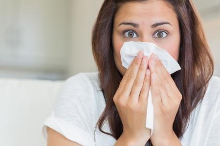 snort: Brunette sneezing into tissue