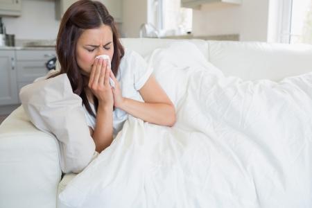 Brunette woman feeling ill on sofa photo