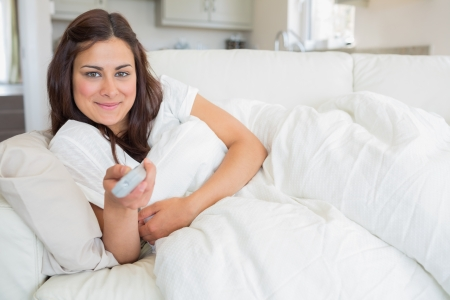 changing channel: Woman changing channel on sofa Stock Photo