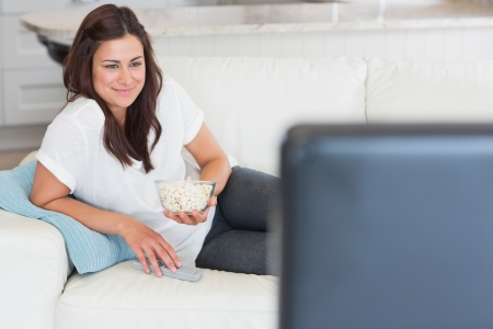 changing channel: Woman enjoying tv with popcorn on sofa
