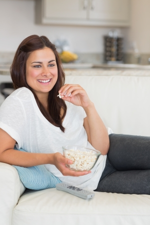 Woman eating popcorn while relaxing on the sofa and smiling photo