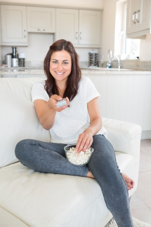 Smiling brunette woman changing the channel on the sofa holding bowl of popcorn photo