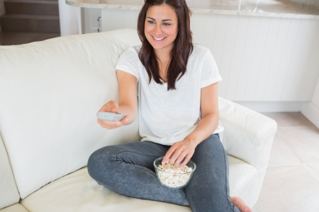 changing channel: Woman smiling and changing channel on sofa Stock Photo