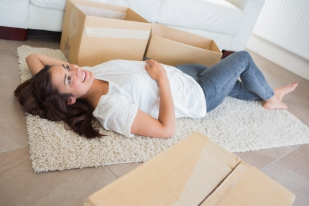 Woman lying on the carpet surrounded by moving boxes in living room photo