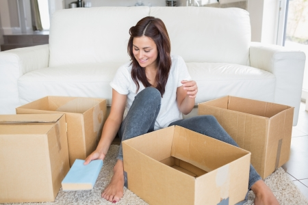 Woman unpacking boxes in living room photo