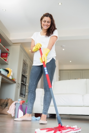 Woman mopping the floor of living room photo
