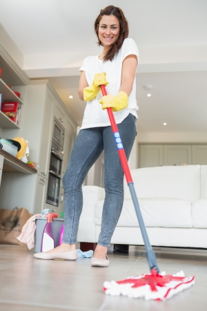 Brunette woman mopping the floor while smiling photo