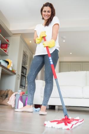 cleaning products: Mujer morena trapear el piso mientras sonreía