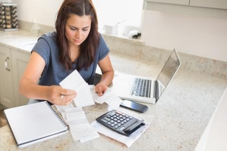 Mujer cálculo de facturas con ordenador portátil en ktichen Foto de archivo