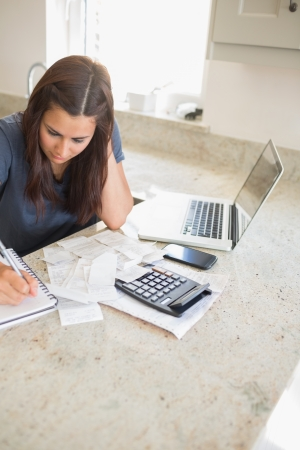 Woman calculating finances in kitchen photo