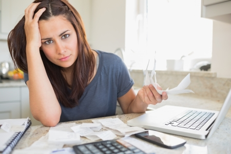 Young woman looking worried over finances in kitchen photo