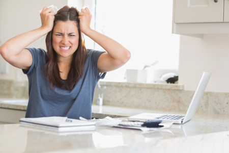 Woman getting frustrated over bills in kitchen Stock Photo - 15590065