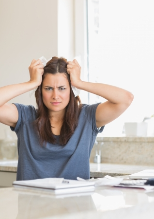 Woman feeling angry about bills in kitchen Stock Photo - 15583380