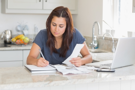 focusing: Woman calculating receipts with laptop in kitchen Stock Photo