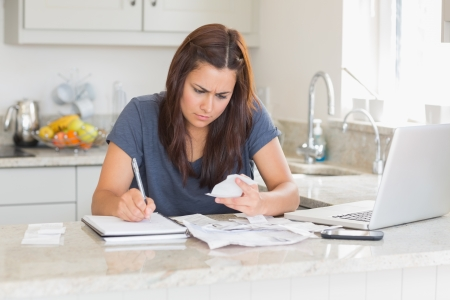Brunette woman calculating bills in the kitchen photo